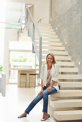 Buy stock photo Portrait of a happy mature woman sitting on modern stairs in a spacious house