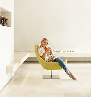 Buy stock photo Happy relaxed mature woman drinking coffee in a designer chair in a modern spacious room