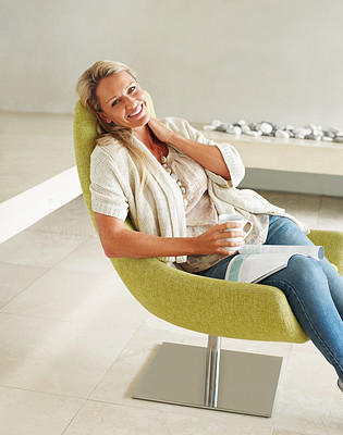 Buy stock photo Portrait of a happy relaxed mature woman sitting in a modern chair with a magazine and coffee cup