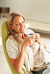 Portrait of a cheerful mature woman drinking coffee