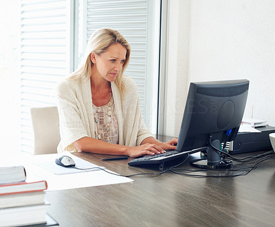 Buy stock photo Portrait of a busy mature female executive at work desk using computer