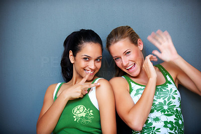 Buy stock photo Portrait of cute young girls making hand gestures and smiling against grey background