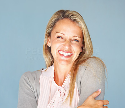 Buy stock photo Closeup portrait of a cheerful woman smiling against blue background