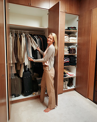 Buy stock photo Image of pretty female looking through her wardrobe and choosing clothes