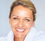 Detail shot of an attractive mature woman smiling against blue