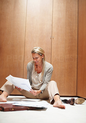 Buy stock photo Relaxed casual mature woman sitting on floor and doing paperwork