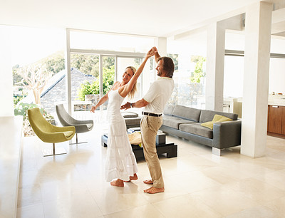 Buy stock photo Romantic mid adult man and woman dancing in a spacious modern living room