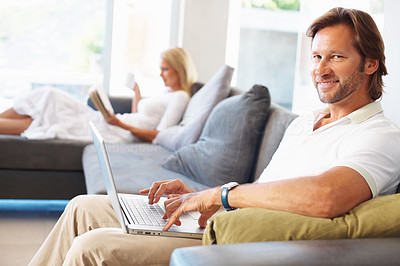 Buy stock photo Portrait of a relaxed mature man using laptop with woman reading book in the background at home