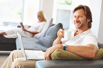Buy stock photo Happy casual man with laptop drinking tea while woman reading book in the background at home
