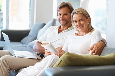 Buy stock photo Portrait of a smiling mature man and woman reading a book and using laptop at home
