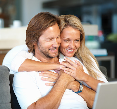 Buy stock photo Loving mature woman embracing man from behind while using laptop at home