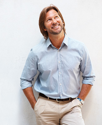 Buy stock photo Portrait of a happy smart mature man smiling over a happy thought , hands in pockets
