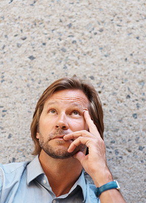 Buy stock photo Portrait of a mature man in a thoughtful pose looking up against wall