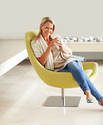 Buy stock photo Portrait of a relaxed mature woman sitting in a modern chair with a magazine and coffee cup