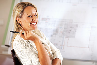 Buy stock photo A happy female architect with architectural plans on her easel - copyspace