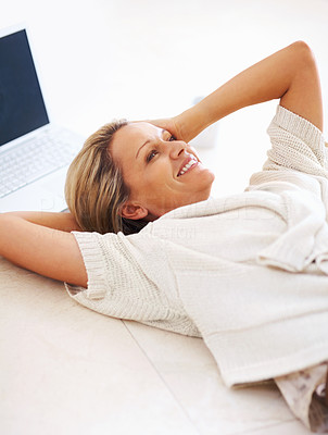 Buy stock photo Thoughtful middle aged woman smiling in her thoughts while lying on floor