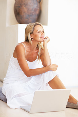 Buy stock photo Portrait of a thoughtful mature woman sitting on floor with laptop
