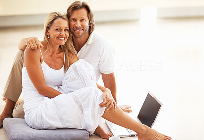 Buy stock photo Portrait of a happy loving mid adult couple sitting on floor with a laptop