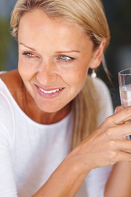 Buy stock photo Detail shot of a thoughtful mature woman holding a glass of water