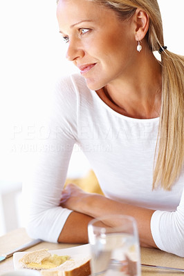 Buy stock photo Portrait of a thoughtful attractive mature woman sitting at breakfast table