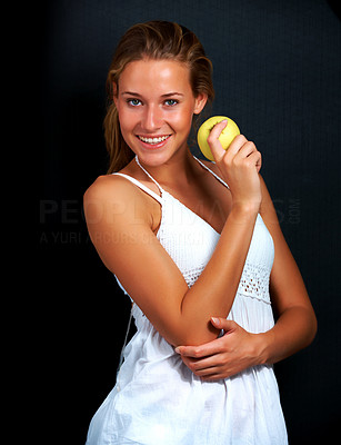 Buy stock photo Portrait of pretty young girl holding an apple posing against black background