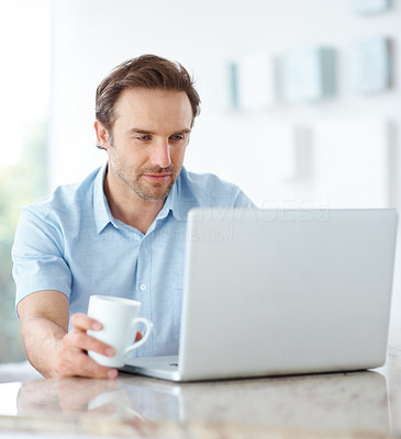 Buy stock photo Portrait of a happy young male holding cup of coffee and using a laptop - Indoor