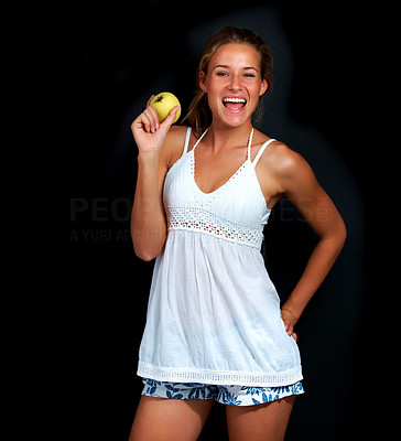 Buy stock photo Portrait of sweet teenage girl holding a apple posing against black background