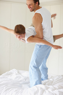 Buy stock photo Portrait of a happy young father playing with his son in the morning