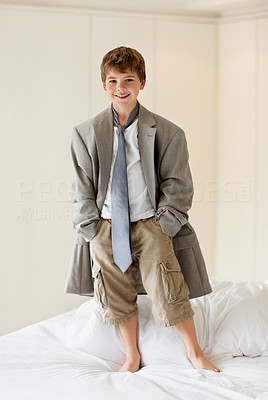 Buy stock photo Portrait of a little boy wearing an oversized coat standing on bed
