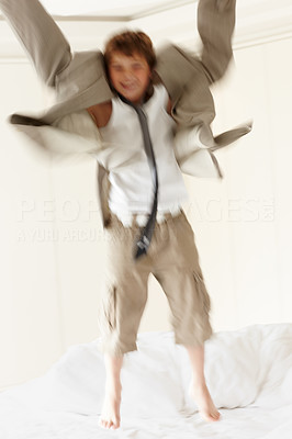 Buy stock photo Portrait of an excited small boy wearing an oversized coat jumping on bed - Indoor