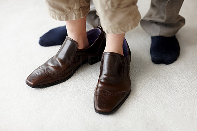 Buy stock photo Low section image of a small young boy wearing his father's shoes