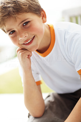 Buy stock photo Portrait of a cute young boy sitting outside and smiling