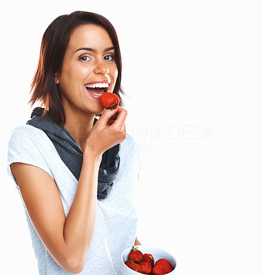 Buy stock photo Young woman eating a bowl of fresh strawberries against white background