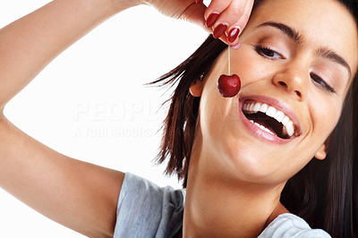 Buy stock photo Closeup of a happy woman holding a cherry to mouth against white background