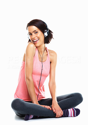 Buy stock photo Happy young woman sitting on floor and listening to music against white background