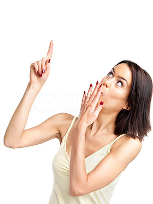 Buy stock photo Portrait of a surprised young woman pointing upwards at copyspace against white background