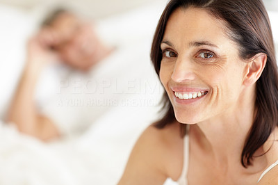 Buy stock photo Closeup of a beautiful mature woman lying on bed with her husband in the background