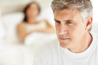 Buy stock photo Closeup of a mature man lying on bed with his wife in the background