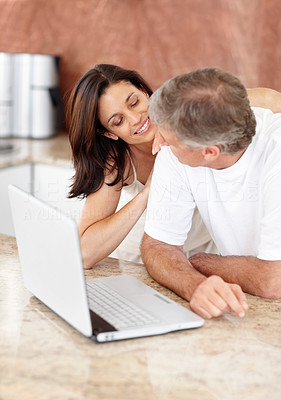 Buy stock photo Portrait of happy mature couple with a laptop computer in the kitchen and looking at each other