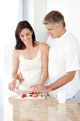Buy stock photo Portrait of  beautiful mature woman cutting fresh fruit with her husband helping her