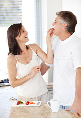 Buy stock photo Portrait of a beautiful mature woman feeding her husband fresh fruit in kitchen