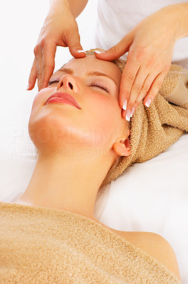 Buy stock photo Shot of a young woman enjoying a face massage at a spa resort.