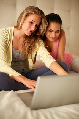 Buy stock photo Portrait of pretty young girls working on laptop while sitting on the bed at home