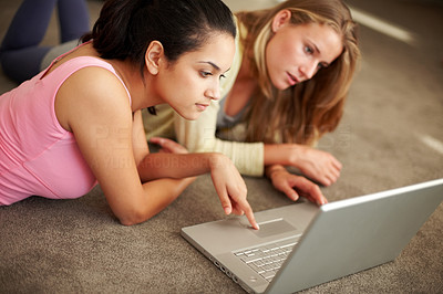 Buy stock photo Portrait of beautiful young girls working together on laptop while lying on the floor
