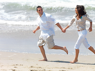 Buy stock photo Young smiling couple running on beach, hand in hand. Laughing and having a fun time.