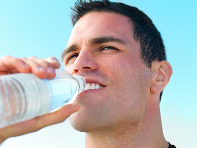 Buy stock photo Close up of a young man drinking water against sky