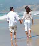 Walking on the beach, wan and woman holding hands.