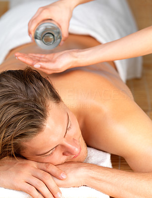 Buy stock photo Happy handsome man getting a back massage. Female hands adding oil. Enjoying a holiday at the beauty spa.