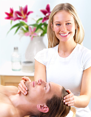 Buy stock photo Portrait of a woman smiling and giving facial massage to young man