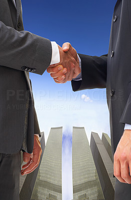 Buy stock photo Cropped shot of two businessmen shaking hands in front of office towers